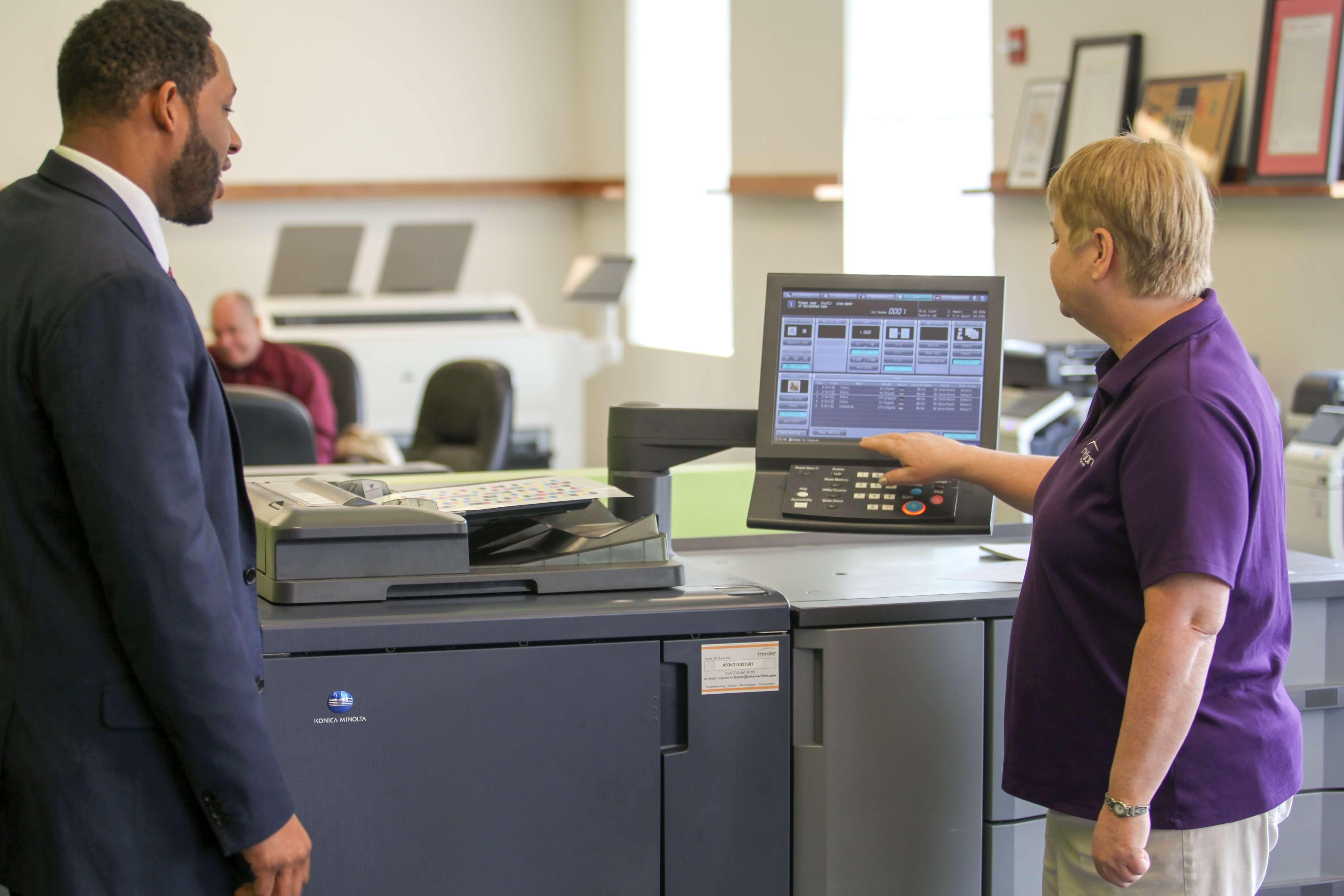 meridian-employees-beth-jason-interacting-with-konica-minolta-production-printer-copier.jpg
