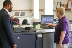 meridian-employees-beth-jason-interacting-with-konica-minolta-production-printer-copier.jpg
